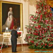White House staff member adjusts paintings before the arrival of the First Lady. Painting of Martha Washington in the background.