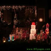 A boxed snow man, toy soldier, candy canes, large multi colored lightbulbs, and white string lights can be seen on this display.