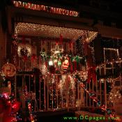 A candy cane reindeer crossing, red bows, santa claus, a Christmas star, a wreath, and many yards of multicolored stringed lights are on display at this home.