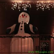 A giant inflatable snowman wearing a top hat, vest, and mittens are on display.