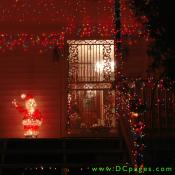 A lit Santa Claus waves on a porch covered in Christmas Lights.