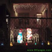 A bright snowman and Santa are accompanied by two white reindeer and a string of white lights.
