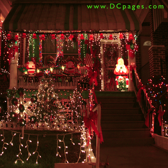 a string of bright christmas bells covers of porch of three santa claus displays