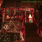 A string of bright Christmas Bells covers of porch of three Santa Claus displays. The yard is decorated with red bows, a lit Christmas tree, and seven mini wreaths.