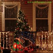 A smiling snowman display, a lit Christmas tree, and strands of white lights can be seen at this home.