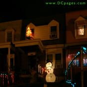 An inflatable snowman holding a candy cane waves to everyone. A reindeer and Santa can be seen on top of the porch. Lit candy canes cover the yard.