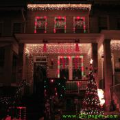"""A Happy Holiday's"" sign with red ribbons on each side showcases a house filled with many outdoor decorations."
