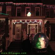 "A brightly lit Santa Claus stands on top of a porch wraped in a strand of classic blue and white lights. A red ribbon, snownen, and garland can be seen. A giant inflatable ""Let it Snow"" globe is in the front of yard."