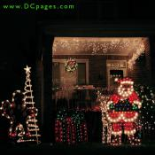 A lit ginger bread man holding a candy cane, Santa Claus, a reindeer, a green and red present, wreath, and lights fill this yard with good cheer.