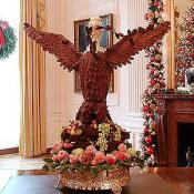 Located in the State Dining room, this eagle made of gold hydrangea leaves stands over a mahogany center table, along with candelabra and urns from the White House vermeil collection