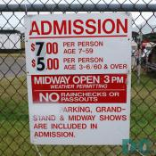 Sign - ADMISSION - $7.00 PER PERSON AGE 7-59 - $5.00 PER PERSON AGE 3-6 and 60 and OVER - MIDWAY OPEN 3 PM - WEATHER PERMITTING - NO RAINCHECKS OR PASSOUTS - PARKING, GRANDSTAND and MIDWAY SHOWS ARE INCLUDED IN ADMISSION.