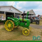 A antique JOHN DEERE tractor is parked in front of the PRINCE WILLIAM ANTIQUE TRACTOR CLUB exhibit barn.