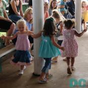 These little girls have fun twirling around a barn pole.