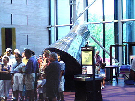 Onlookers pass the Mercury Space capsule in the front lobby.