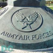 A bronze flag base adorned with the military service seals of the Army, Navy, Marine Corps, Army Air Forces, Coast Guard and Merchant Marine.