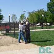 Workers take down the fence from the perimeter of the World War II Memorial.