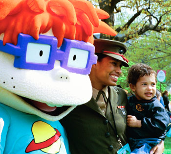 "A United States Marine and her son stand for pictures with Chuckie, a character from the cartoon, ""Rugrats."""