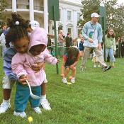 A helping hand is given during the Easter egg roll where little competitors use a spoon to carry a hard-boiled egg through the South Lawn race course and across the finish line
