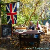 A smiling colonial woman welcomes guests to the Market Fair. There is a British 'Union Jack' flag hangs on the left representing the time when this area was under English rule.