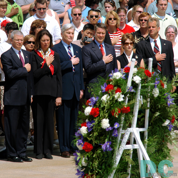 Senator John Warner, and other Americans place their hand over their hearts while Taps plays at the Tomb of the Unknowns during Memorial Day ceremonies, May 29, 2006 at Arlington National Cemetery.