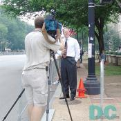 A TV news reporter provides live coverage to his local area news.