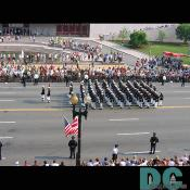 The U.S. Marines marching while receiving cheers from the crowd.